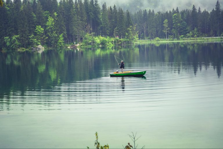 Man on a green boat fishing on lake