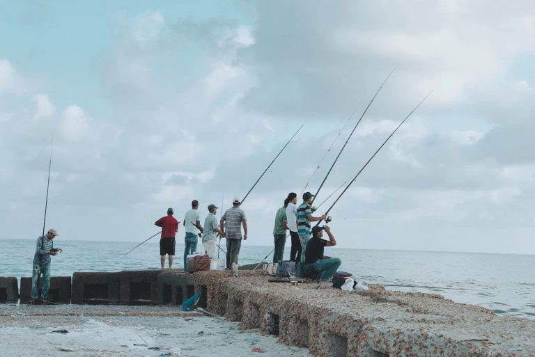 People with fishing rods by the sea