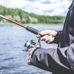 Person fishing on a sunny day holding a red and black fishing rod