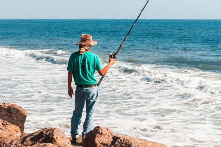 Person standing on rocks by the sea holding a fishing pole