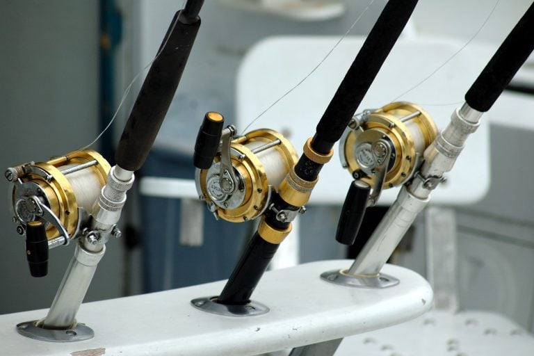 Three gold fishing reels and three black and silver fishing rods on a mount