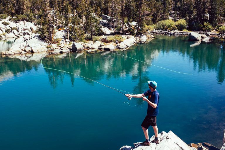 Man Fly Fishing by a Lake