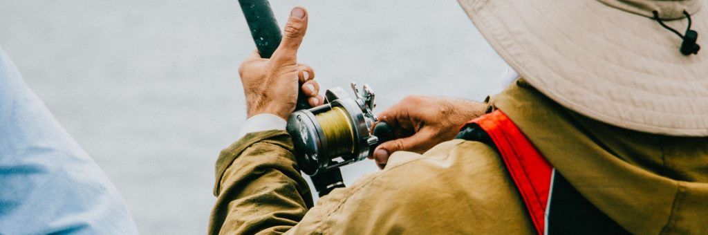 Casting Reel Held by a Fisherman