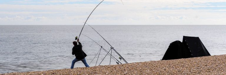 Fisherman Casting a Reel on a Beach