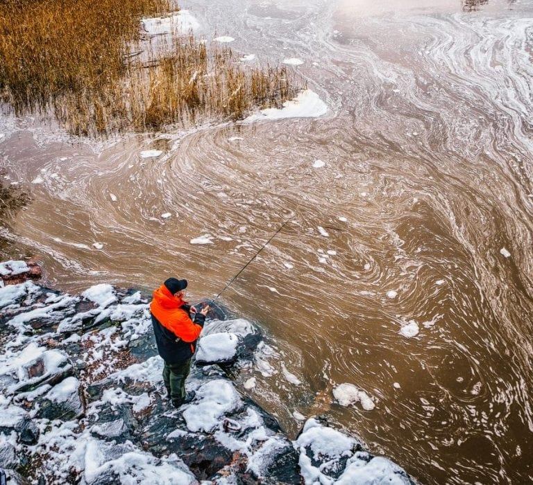 Man Fishing in the Winter Using Combo Reel