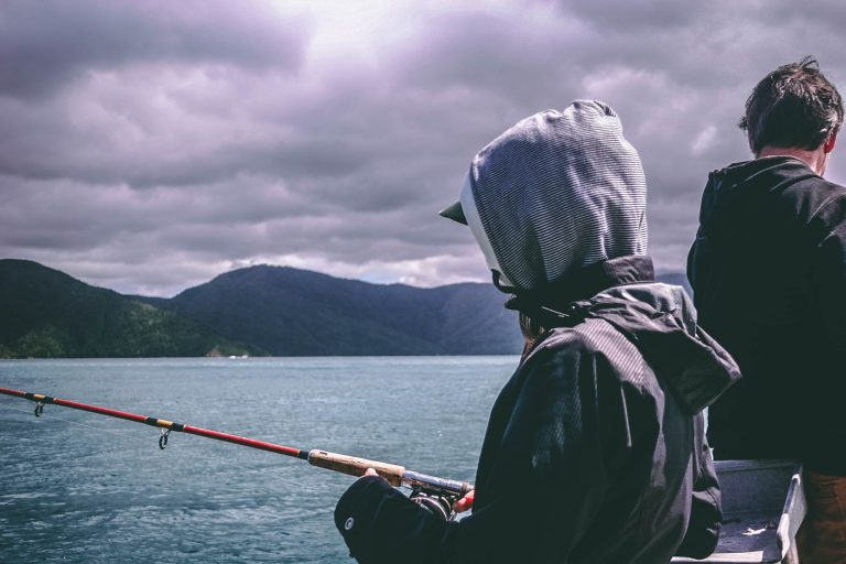 Hooded Person Fishing on a Boat