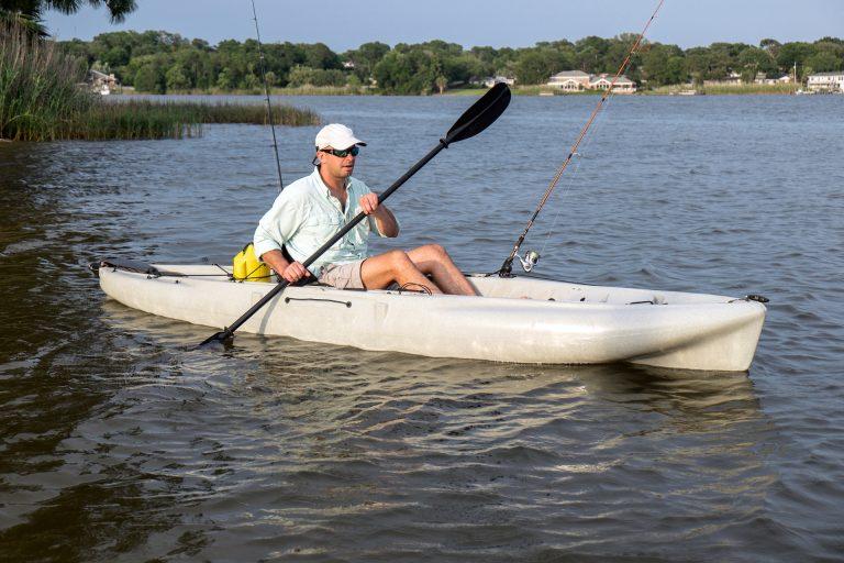 Man Paddling a White Kayak