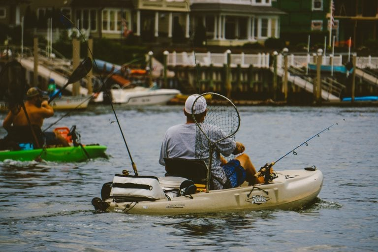Man on a Kayak Carrying Different Fishing Gears