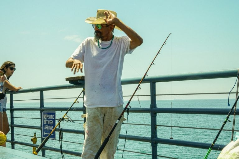 Fisherman on a Pier Wearing a Hat