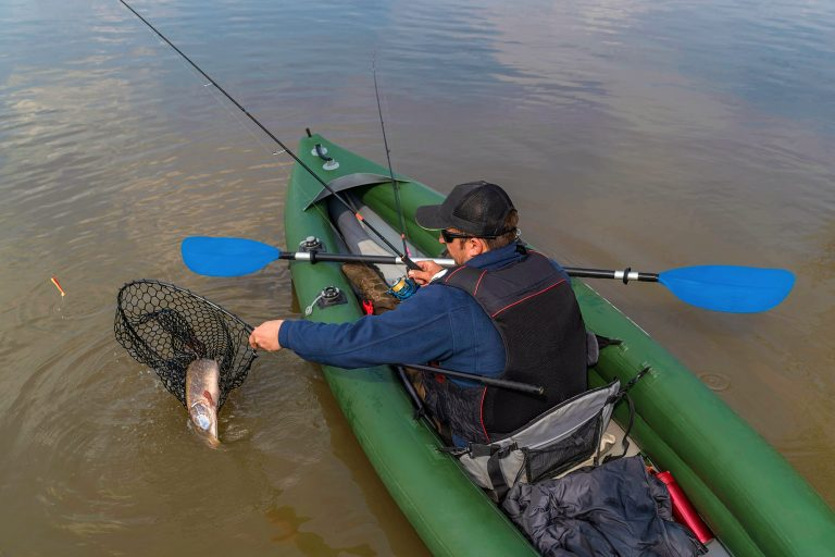 Man on a Kayak Putting Fish on a Net