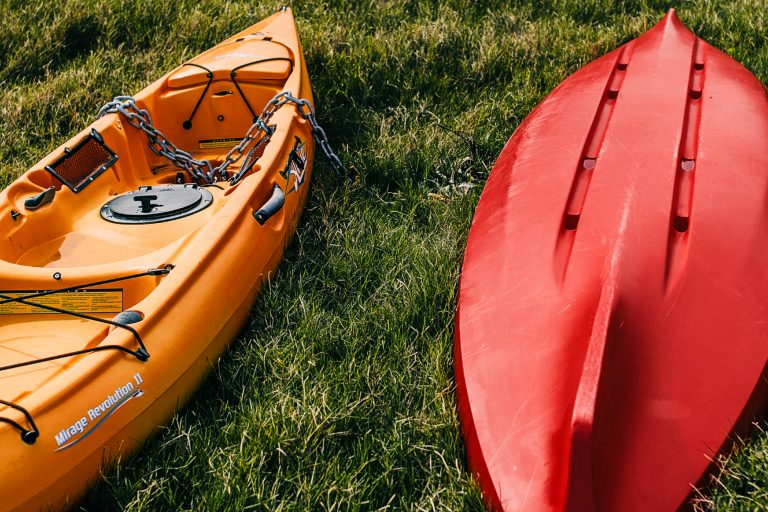 Red and Orange Kayak on Top of Grass