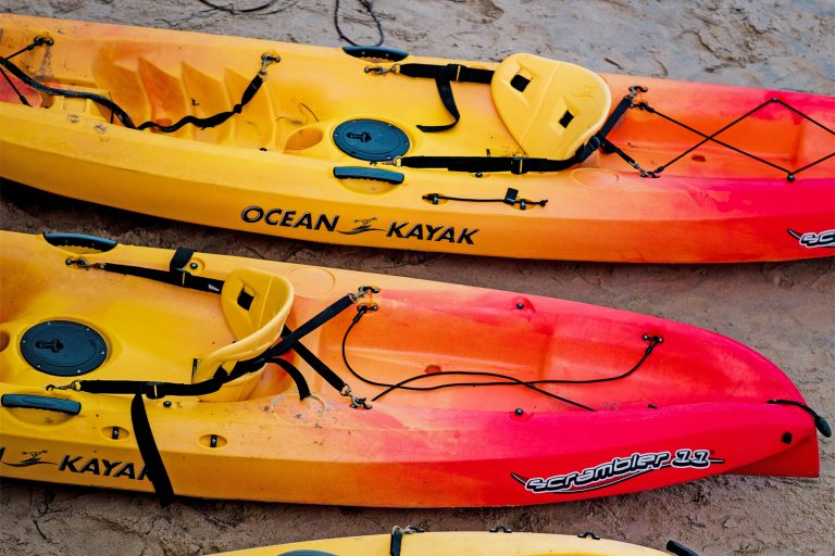 Red and Yellow Sit on Top Kayaks on a Beach