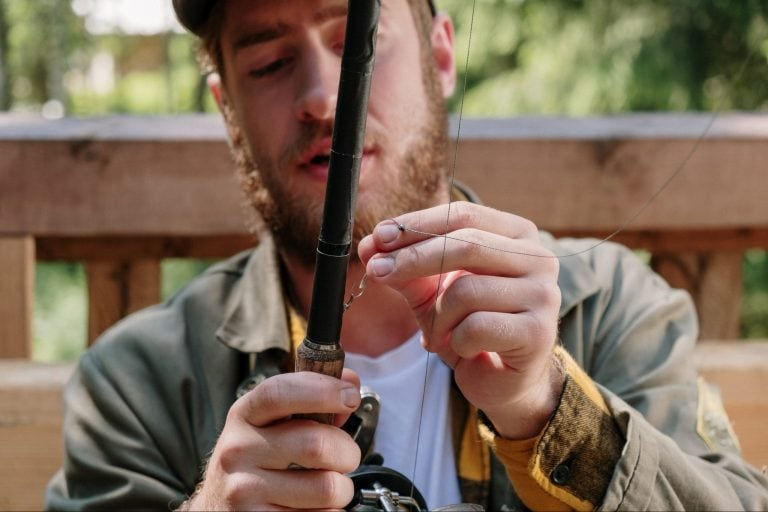 A close up of a man setting up his rod