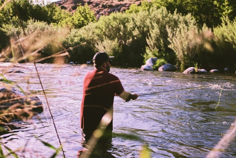A shot of a man's back in a red shirt fishing in a river