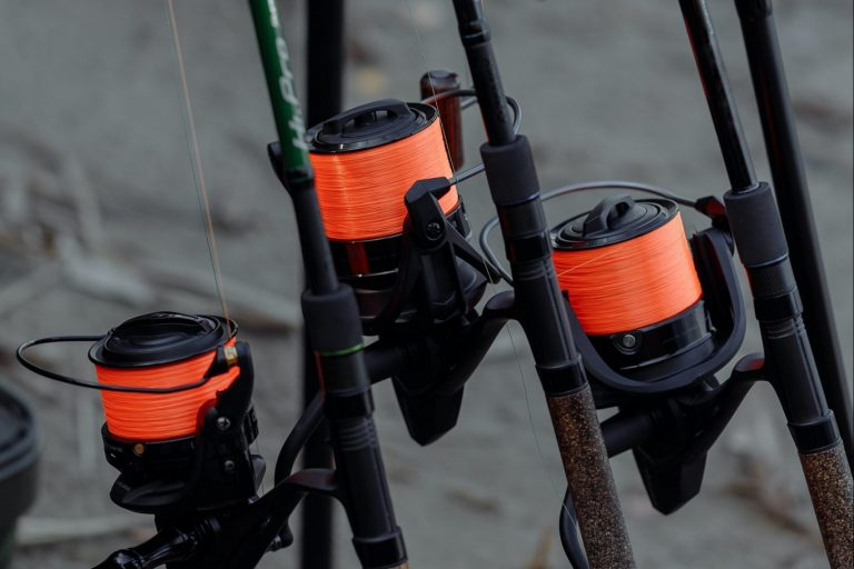 A shot of a 3 fishing reels on separate upright rods
