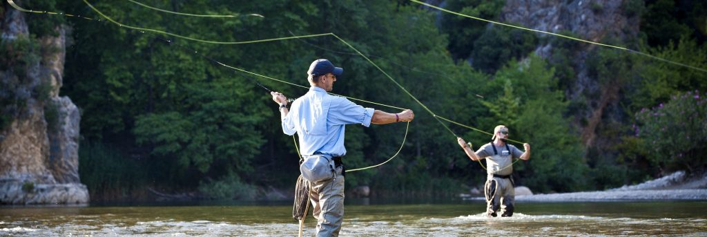 Two men casting rods in a river